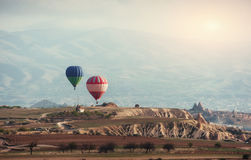 Ζωηρόχρωμα μπαλόνια ζεστού αέρα που πετούν πέρα από την κόκκινη κοιλάδα σε Cappadocia, Στοκ Εικόνες