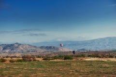 Ζωηρόχρωμα μπαλόνια ζεστού αέρα που πετούν πέρα από την κόκκινη κοιλάδα σε Cappadocia, Στοκ Φωτογραφίες