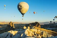 Ζωηρόχρωμα μπαλόνια ζεστού αέρα που πετούν πέρα από τις αρχαίες κοιλάδες σε Cappado Στοκ Φωτογραφίες