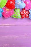 Ζωηρόχρωμα παιχνίδια Χριστουγέννων Αισθητά χριστουγεννιάτικα δέντρα, γάντια, καρδιές, αστέρια στον ιώδη ξύλινο πίνακα με την κενή Στοκ Εικόνα