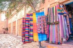 Ζωηρόχρωμα παραδοσιακά μαροκινά μαντίλι και σάλια που κρεμούν σε ένα δέντρο για την πώληση Ouarzazate, Μαρόκο στοκ εικόνες με δικαίωμα ελεύθερης χρήσης