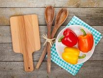 Ζωηρόχρωμα πιπέρια κουδουνιών και εργαλεία κουζινών Στοκ Εικόνες
