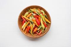Ζωηρόχρωμα πιπέρια τσίλι στο ξύλινο πιάτο Στοκ Φωτογραφία