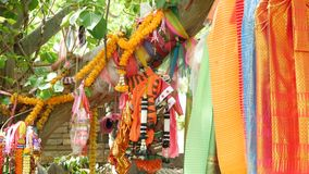 Ζωηρόχρωμα προσφέροντας ενδύματα στο δέντρο κοντά στο βωμό Δέσμη των φωτεινών παραδοσιακών ενδυμάτων ως δώρο στα ταϊλανδικά πνεύμ απόθεμα βίντεο