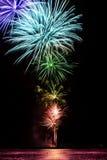 Ζωηρόχρωμα πυροτεχνήματα των διάφορων χρωμάτων πέρα από το νυχτερινό ουρανό Στοκ Φωτογραφία
