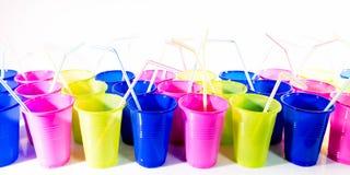 Ζωηρόχρωμα πλαστικά φλυτζάνια με τα άχυρα κατανάλωσης Στοκ φωτογραφία με δικαίωμα ελεύθερης χρήσης