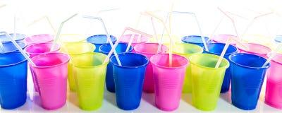 Ζωηρόχρωμα πλαστικά φλυτζάνια με τα άχυρα κατανάλωσης Στοκ Φωτογραφίες