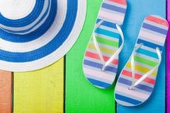 Ζωηρόχρωμα σανδάλια και καπέλο στο θαυμάσιο ζωηρόχρωμο ξύλινο backgr Στοκ φωτογραφία με δικαίωμα ελεύθερης χρήσης