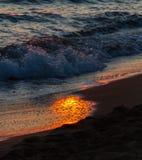 Ζωηρόχρωμα σπάζοντας κύματα στις αντανακλάσεις ακτών και ήλιων στο ηλιοβασίλεμα Στοκ εικόνα με δικαίωμα ελεύθερης χρήσης