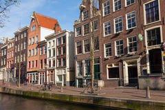 Ζωηρόχρωμα σπίτια διαβίωσης κατά μήκος του αναχώματος καναλιών στο Άμστερνταμ Στοκ Εικόνα