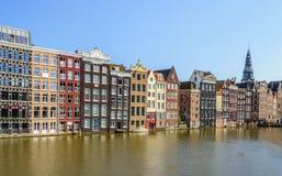 Ζωηρόχρωμα σπίτια καναλιών στο Damrak στο ολλανδικό κύριο Amsterd Στοκ Φωτογραφία