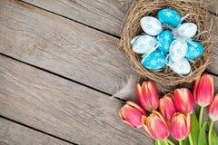 Ζωηρόχρωμα τουλίπες και αυγά Πάσχας στη φωλιά στον ξύλινο πίνακα Στοκ Εικόνες