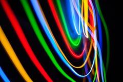 Ζωηρόχρωμα φωτεινά κόκκινα, κίτρινα, μπλε και πράσινα μικτά φω'τα Χριστουγέννων που ρέουν στις διάφορες κατευθύνσεις στοκ φωτογραφίες