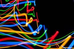 Ζωηρόχρωμα φωτεινά κόκκινα, κίτρινα, μπλε και πράσινα μικτά φω'τα Χριστουγέννων που ρέουν στις διάφορες κατευθύνσεις στοκ φωτογραφία με δικαίωμα ελεύθερης χρήσης