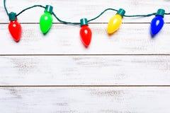 Ζωηρόχρωμα φω'τα Χριστουγέννων σε ένα άσπρο ξύλινο slat υπόβαθρο στοκ εικόνα