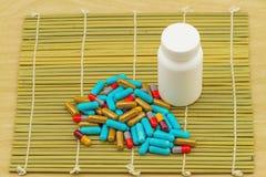Ζωηρόχρωμα χάπια και άσπρες ταμπλέτες μπουκαλιών στην καφετιά ύφανση μπαμπού Στοκ φωτογραφίες με δικαίωμα ελεύθερης χρήσης