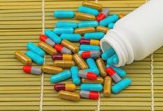 Ζωηρόχρωμα χάπια και άσπρες ταμπλέτες μπουκαλιών στην καφετιά ύφανση μπαμπού Στοκ Εικόνα