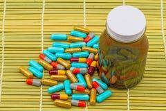 Ζωηρόχρωμα χάπια και μαύρες ταμπλέτες μπουκαλιών στην καφετιά ύφανση μπαμπού Στοκ φωτογραφία με δικαίωμα ελεύθερης χρήσης