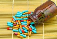 Ζωηρόχρωμα χάπια και μαύρες ταμπλέτες μπουκαλιών στην καφετιά ύφανση μπαμπού Στοκ εικόνες με δικαίωμα ελεύθερης χρήσης
