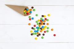 Ζωηρόχρωμα χάπια καραμελών σοκολάτας στην άσπρη ξύλινη κορυφή υποβάθρου Στοκ φωτογραφία με δικαίωμα ελεύθερης χρήσης