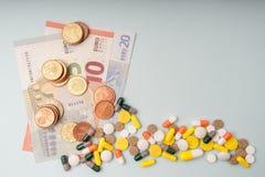 Ζωηρόχρωμα χάπια στο υπόβαθρο των διάφορων ευρο- τραπεζογραμματίων και των νομισμάτων με το διάστημα για το κείμενο στοκ φωτογραφίες με δικαίωμα ελεύθερης χρήσης