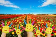 Ζωηρόχρωμα χέρια με τα χρωματισμένα πρόσωπα ενάντια στους τομείς λουλουδιών Στοκ Φωτογραφία