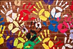 Ζωηρόχρωμα χέρια σε ένα brickwall Στοκ Εικόνα