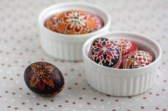 Ζωηρόχρωμα χρωματισμένα αυγά Πάσχας στα άσπρα κύπελλα στο διαστιγμένο τραπεζομάντιλο, παραδοσιακή όμορφη ζωή Πάσχας ακόμα στοκ φωτογραφία με δικαίωμα ελεύθερης χρήσης