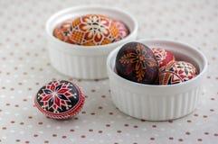 Ζωηρόχρωμα χρωματισμένα αυγά Πάσχας στα άσπρα κύπελλα στο διαστιγμένο τραπεζομάντιλο, παραδοσιακή όμορφη ζωή Πάσχας ακόμα στοκ φωτογραφίες