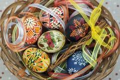 Ζωηρόχρωμα χρωματισμένα αυγά Πάσχας στο καφετί ψάθινο καλάθι που καλύπτεται με τις ζωηρόχρωμες κορδέλλες, παραδοσιακή ζωή Πάσχας  στοκ εικόνες
