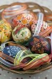 Ζωηρόχρωμα χρωματισμένα αυγά Πάσχας στο καφετί ψάθινο καλάθι που καλύπτεται με τις ζωηρόχρωμες κορδέλλες, παραδοσιακή ζωή Πάσχας  στοκ φωτογραφίες με δικαίωμα ελεύθερης χρήσης