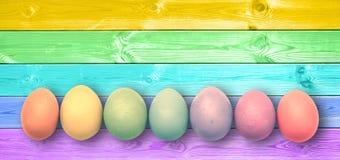 Ζωηρόχρωμα χρωματισμένα ουράνιο τόξο αυγά κρητιδογραφιών, πανοραμικές ξύλινες σανίδες, υπόβαθρο Πάσχας στοκ εικόνες