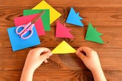 Ζωηρόχρωμα ψάρια Origami, φύλλα εγγράφου, ψαλίδι Το παιδί κρατά το φύλλο εγγράφου στα χέρια του και την κατασκευή των ψαριών orig Στοκ φωτογραφία με δικαίωμα ελεύθερης χρήσης