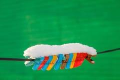 Ζωηρόχρωμα clothespins στη σκοινί για άπλωμα που καλύπτεται με το χιόνι υπαίθρια καλυμμένα όρη σπιτιών ελβετικά χειμερινά δάση χι στοκ φωτογραφίες