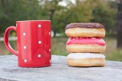 Ζωηρόχρωμα donuts με το κόκκινο φλιτζάνι του καφέ Στοκ φωτογραφίες με δικαίωμα ελεύθερης χρήσης