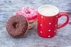 Ζωηρόχρωμα donuts με το κόκκινο φλιτζάνι του καφέ Στοκ εικόνα με δικαίωμα ελεύθερης χρήσης