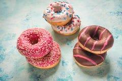 Ζωηρόχρωμα donuts στον πίνακα μπλε πετρών Τοπ όψη Στοκ Φωτογραφία