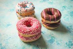 Ζωηρόχρωμα donuts στον πίνακα μπλε πετρών Τοπ όψη Στοκ Εικόνες