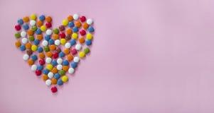 Ζωηρόχρωμα dragees που διαμορφώνουν μια καρδιά Στοκ φωτογραφία με δικαίωμα ελεύθερης χρήσης