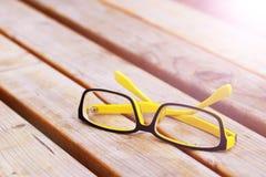 Ζωηρόχρωμα Eyeglasses σε έναν πάγκο πάρκων Στοκ Εικόνες