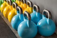 Ζωηρόχρωμα kettlebells σε μια σειρά σε μια γυμναστική - εστιάστε στο μπροστινό kett Στοκ εικόνα με δικαίωμα ελεύθερης χρήσης