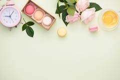 Ζωηρόχρωμα macaroons και αυξήθηκαν λουλούδια με το κιβώτιο δώρων στο ξύλινο tabl στοκ εικόνα