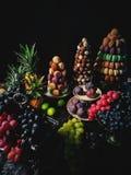 ζωηρόχρωμα macaroons, χειροποίητες καραμέλες σοκολάτας, ανανάς, σύκα, σταφύλια, πίνακας επιδορπίων στοκ εικόνες με δικαίωμα ελεύθερης χρήσης