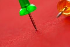 Ζωηρόχρωμα pushpins σε μια κόκκινη επιφάνεια Στοκ Φωτογραφίες