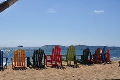 Ζωηρόχρωμες έδρες Adirondack σε μια αμμώδη παραλία στοκ εικόνες