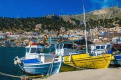 Ζωηρόχρωμες βάρκες: μπλε-άσπρος και κίτρινος στον ελληνικό λιμένα Στοκ Φωτογραφία
