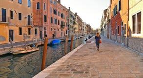 Ζωηρόχρωμες γωνίες και παλαιά κτήρια με το κανάλι και τη γυναίκα νερού στο εξαφανιμένος σημείο στη Βενετία, Ιταλία στοκ φωτογραφία με δικαίωμα ελεύθερης χρήσης