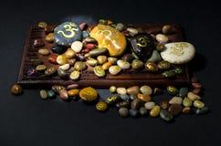 Ζωηρόχρωμες διακοσμητικές πέτρες που χρωματίζονται με το σύμβολο του OM Στοκ Εικόνες
