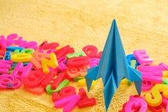 Ζωηρόχρωμες επιστολές αλφάβητου με τον μπλε πύραυλο origami παιχνιδιών η εκπαίδευση έννοιας βιβλίων απομόνωσε παλαιό Στοκ Φωτογραφίες