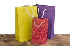 Ζωηρόχρωμες και φωτεινές συσκευασίες αγορών για τα δώρα στον ξύλινο πίνακα Στοκ εικόνα με δικαίωμα ελεύθερης χρήσης